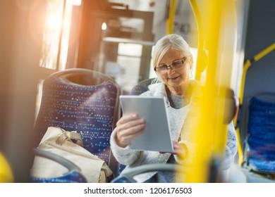 Senior passenger using digital tablet on a bus