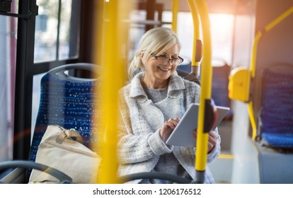 Senior passenger using digital tablet on a bus