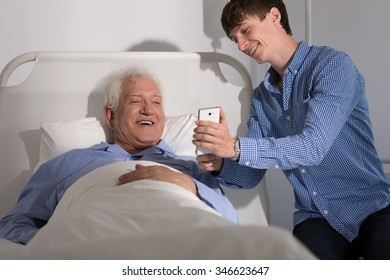 Senior patient in bed visited by his young grandson