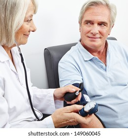Senior patient at blood pressure measurement smiling at doctor