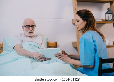 Senior patient and caregiver using tablet