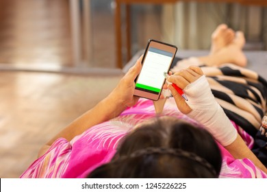 Senior patient hand injured with bandage lying down and using cell phone.