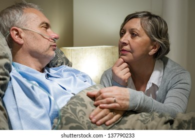 Senior patient at hospital with worried wife holding hands
