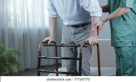 Senior patient of nursing home moving with walking frame and nurse support