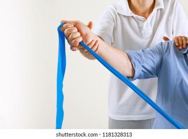 Senior patient undergoing rehabilitation with a blue elastic