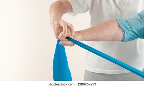 Senior patient undergoing rehabilitation with a blue stretch band ( with photographic effect)