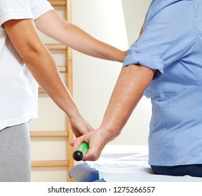 Senior patient undergoing rehabilitation with a green gymnastic stick