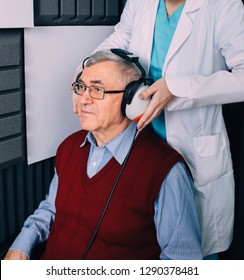 Senior patient wearing headphones, sitting at soundproof cabin, during ear exam at audiologists office