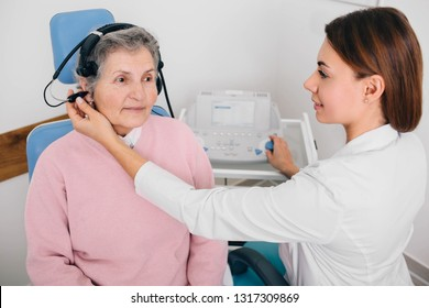 Senior patient wearing headphones, sitting near audiologist during ear exam at hearing clinic