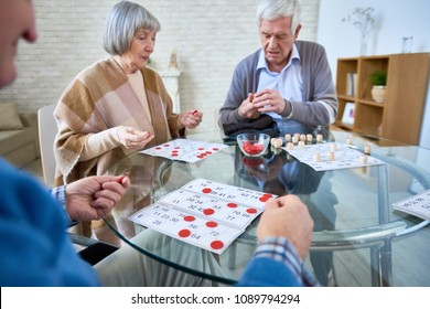 Senior patients of assisted living home gathering at table in living room and playing lotto at table.