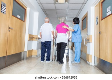 Senior patients being assisted by female asian nurse in using walker.
