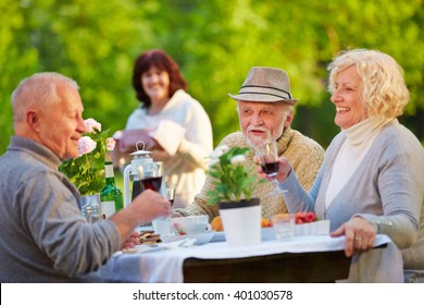 Senior people celebrating birthday in garden with cake and wine