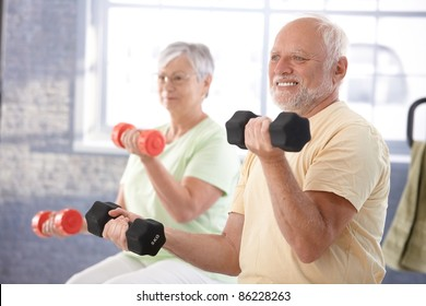 Senior people doing dumbbell exercises in the gym.?