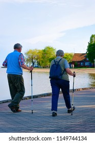 Senior people doing nordic walking at Nida town near Klaipeda in Neringa at the Curonian Spit and the Baltic Sea in Lithuania.