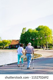 Senior people doing nordic walking in Nida town near Klaipeda in Neringa at the Curonian Spit and the Baltic Sea in Lithuania.