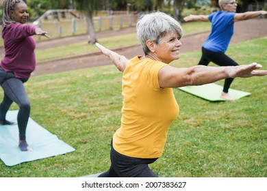 Senior people doing yoga class keeping distance at city park - Focus on center woman face