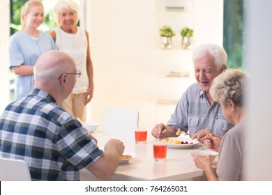 Senior people eating dinner while sitting at a table in nursing house