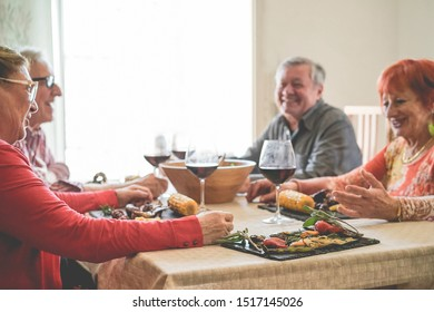 Senior people eating vegetarian food and drinking wine inside vintage trendy restaurant - Old people having fun at meal lunch - Joyful elderly lifestyle concept - Focus on close-up vegetables