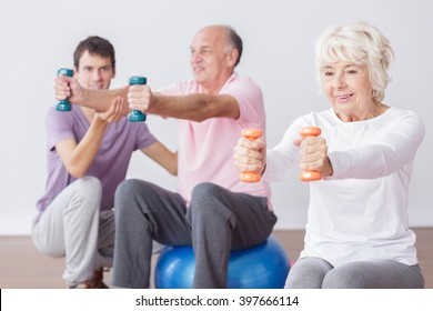 Senior people exercising with dumbbells and gym balls with fitness instructor.