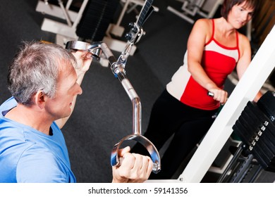 Senior people in a gym exercising on a pulldown machine