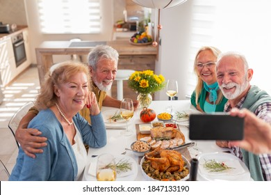 Senior people having fun while celebrating Thanksgiving together at home over traditional dinner, taking a selfie using smart phone