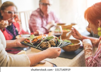 Senior people having vegetarian lunch at home - Mature friends eating bbq vegetables,fresh salads and drinking red wine - Healthy and vegan concept - Focus on artichoke bottom dish