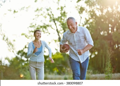 Senior people playing american football together outside in summer