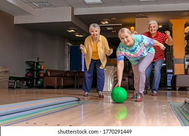 Senior people playing bowling in club