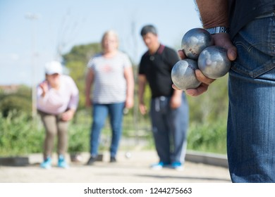 senior people prepared to throw the boules ball in a park in outdoor play