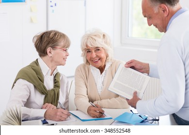 Senior people reading book together in the library