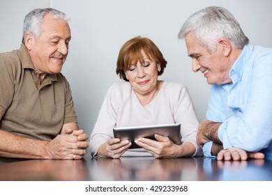 Senior People Using Digital Tablet In Classroom