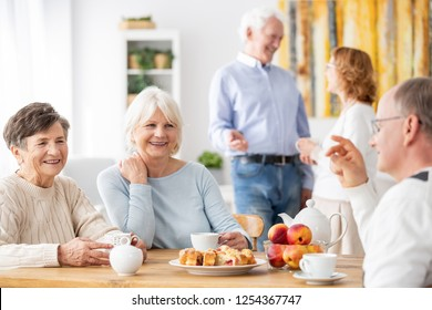 Senior people visiting old friends at home sitting together at wooden table chatting, drinking tea and eating cake