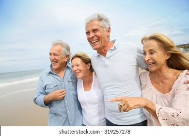 Senior people walking on the beach