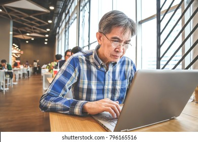 Senior person in 50 years old using laptop for searhing information in business and learning for education in the co working space.