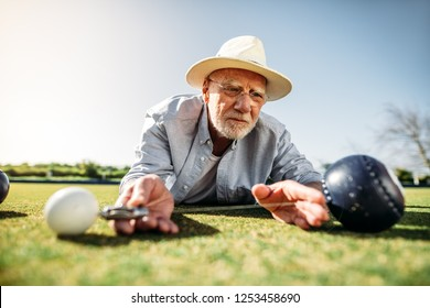 Senior person checking the distance between a boules and the jack for the result. Senior man measuring the distance between boules closely using a measuring device lying on the ground.