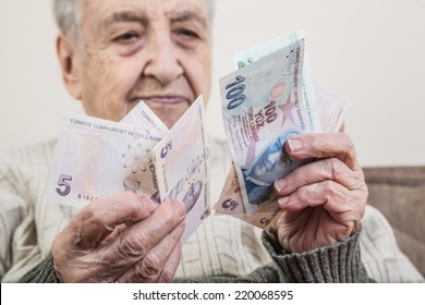 a senior person holding money (turkish lira)