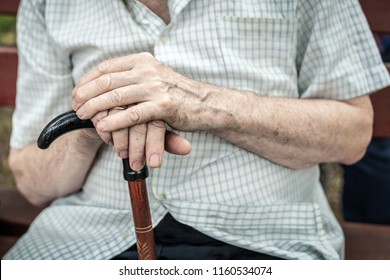 Senior person sitting on wooden bench outdoors. Old man hands holding walking stick. Poverty, loneliness and hopelessness concept