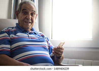Senior person smiling with smartphone sitting in an armchair with a striped polo shirt next to a very bright window