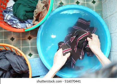 Senior person washing clothes with her hands