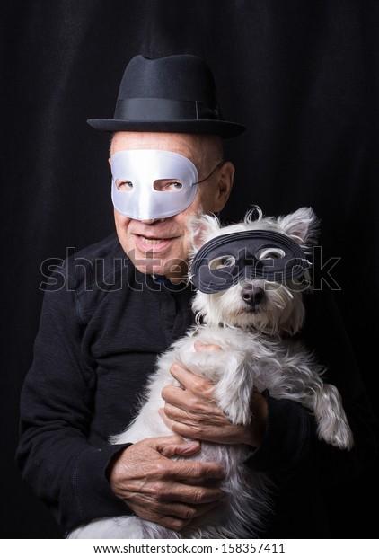 A senior pet owner and dog dressed alike in masks for Halloween.