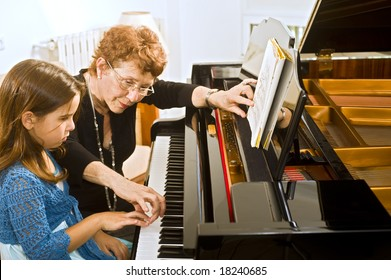 senior piano teacher with young girl student