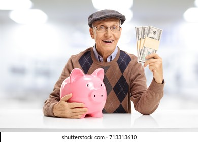 Senior with a piggybank and bundles of money seated at a table