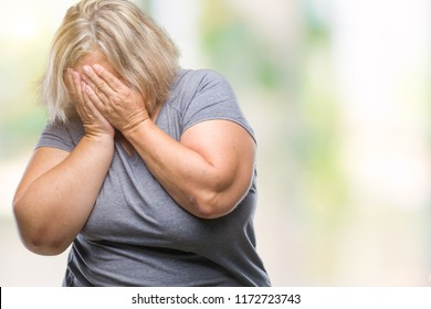 Senior plus size caucasian woman over isolated background with sad expression covering face with hands while crying. Depression concept.