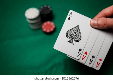 Senior Poker. Four playing cards, four aces and poker chips on a green casino table / on a black background. Card deck / poker. success in gambling. The player holds four aces in his hand. soft focus
