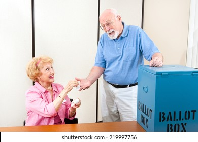 Senior poll worker giving an I Voted sticker to an elderly male voter.