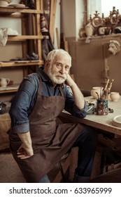 Senior potter in apron sitting at table and looking at camera at manufacturing
