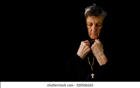 A senior praying woman between 70 and 80 years old, dressed in black. Free space for a text. Front  view
