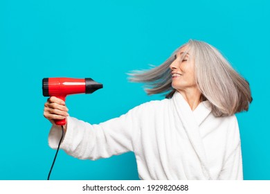 senior pretty woman after shower wearing bathrobe. hairdryer concept