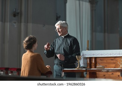 Senior priest blessing the faithful woman in the church - Shutterstock ID 1962860326
