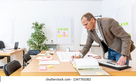 Senior production manager going over design drawings for final approval and revisions in a large, brightly lit office with production planning boards on the walls.
